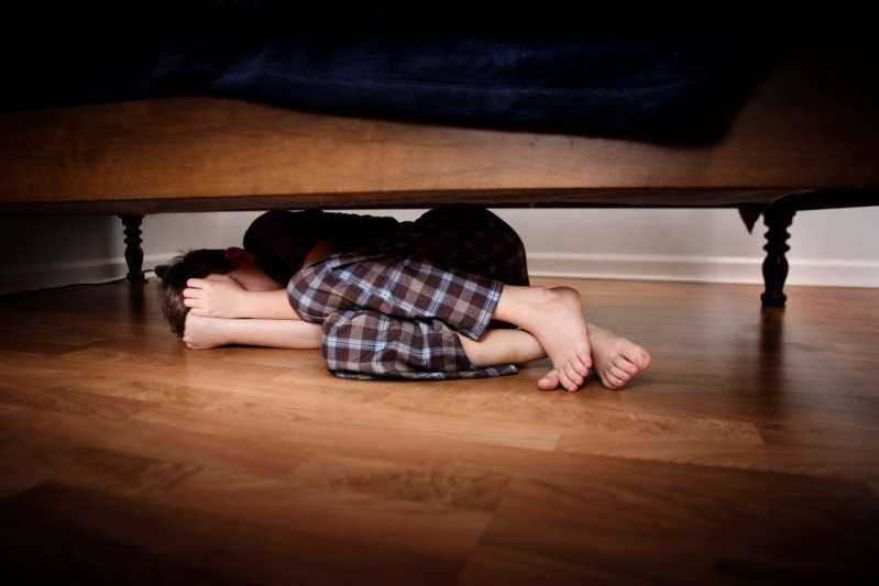 Mom Leaves 4 Underage Kids Home Alone As She Travels Miles Away To Go On Vacation. Is This Right For A Parent?Emotional abuse: fearful boy hiding under the bed