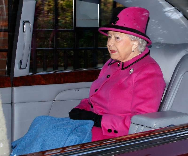 the queen in her car, the queen is traveling with a blanket