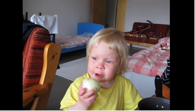 Hilarious Kid Stubbornly Eats Onion And Think Its An Apple In A Viral Video daughter eats onion