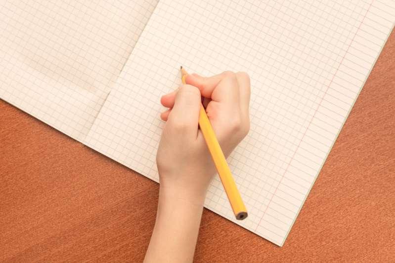 La note de cet élève qui explique pourquoi il n'a pas fait ses devoirs en a fait un véritable héro sur internethand of a schoolgirl writes a pen in notebook