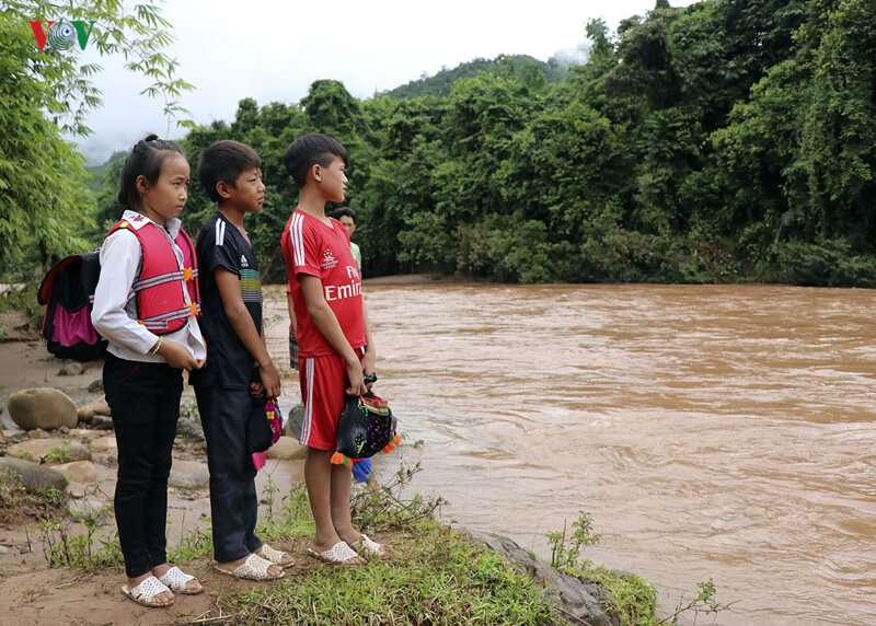 Mann mit Kindern im Plastiksack überquert angeschwollenen Fluss, damit sie zur Schule gehen können