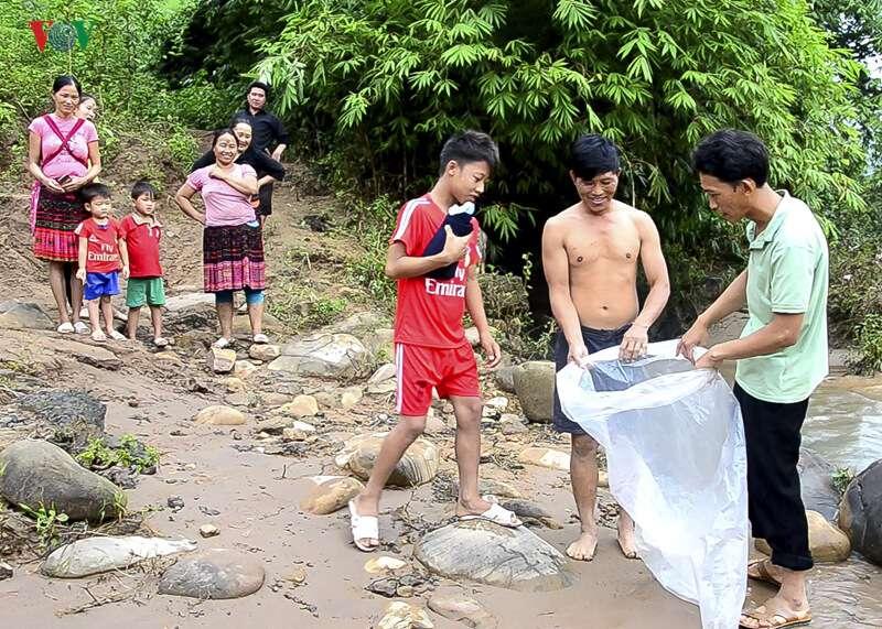 Il traverse une rivière en crue avec des enfants dans un sac en plastique afin qu'ils puissent aller à l'école