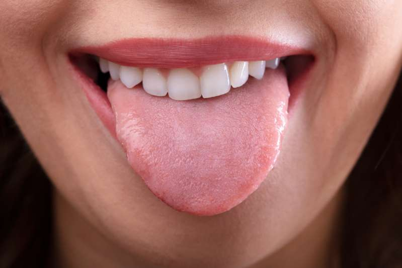 When Do Teeth Marks On The Tongue Signal Health Problems?Close-up Of A Woman's Face Showing Her Clean Tongue