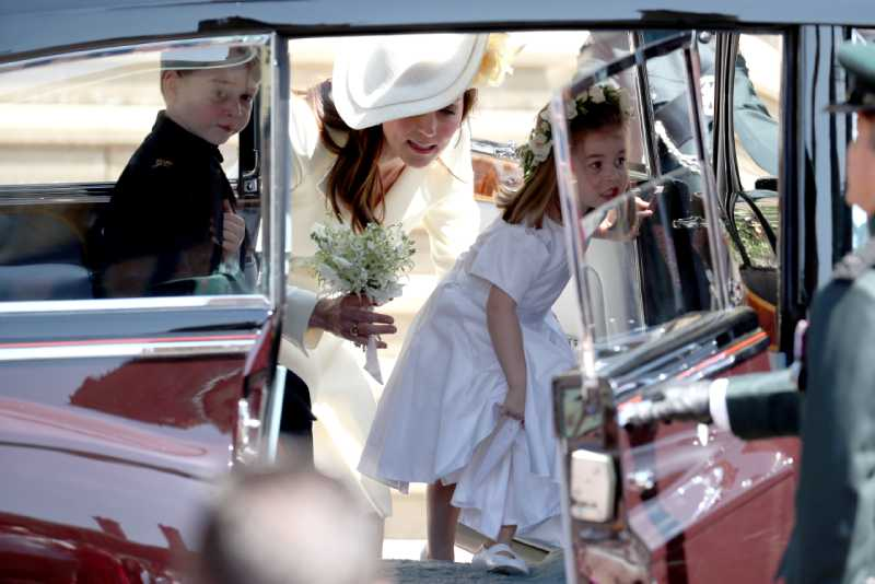 Prince George of Cambridge (L) and Princess Charlotte of Cambridge (R) step inside their car with their mother Catherine