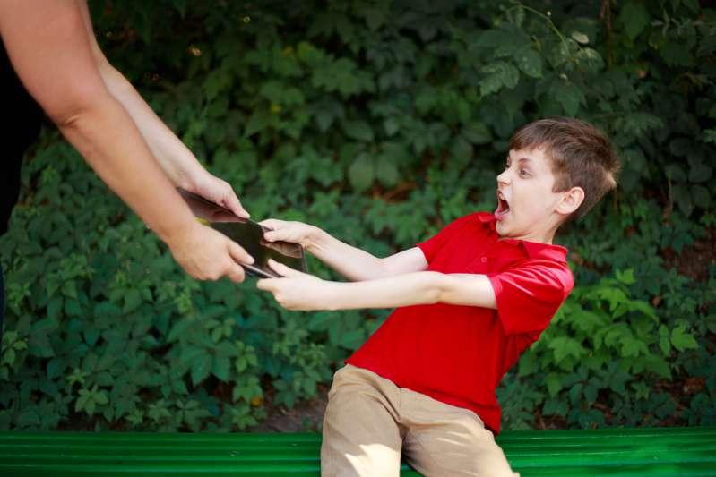Зависимость от видеоигр: горькая правда, которую должен знать каждый родительElectronic games addiction. Mother taking tablet away from the addicted child.