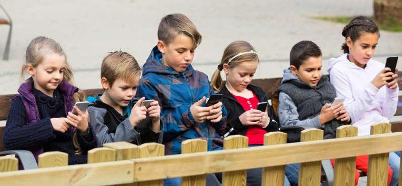 Зависимость от видеоигр: горькая правда, которую должен знать каждый родительGroup of smiling children posing at urban street with mobile devices