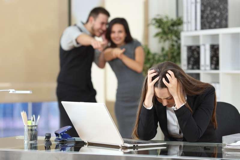 Die häufigsten Arten von Mobbing: wie erkennt man, dass jemand gemobbt wird?Two adults bullying a sad colleague that is sitting in her workplace at office
