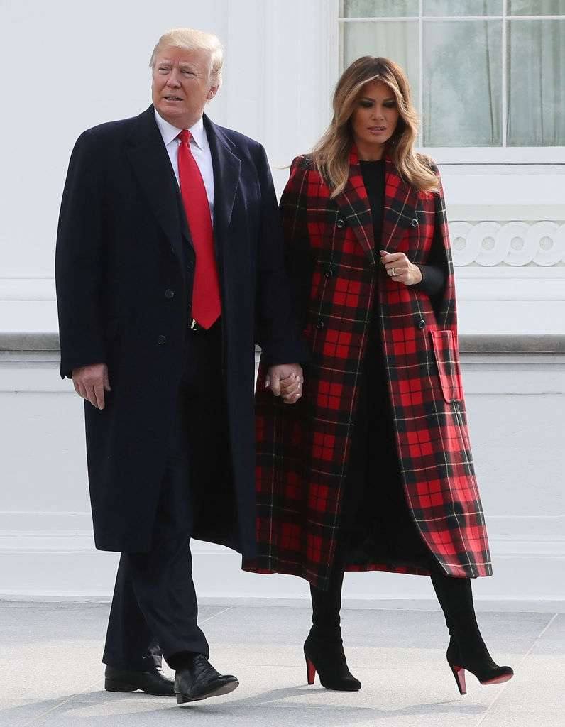 Melania Looked Festive In A Classy Red And Black Coat Next To Horse And Carriage With A Christmas Tree