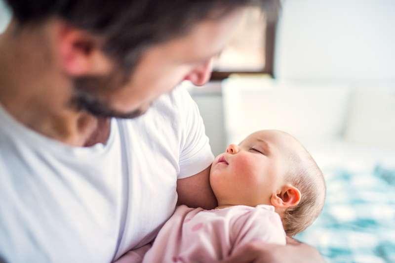 Une maman trouve une astuce géniale pour que son bébé reste endormi quand elle prend une douche ou un caféFather holding a sleeping toddler girl at home