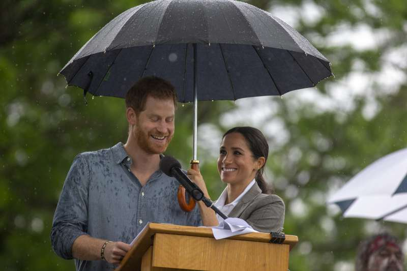 She'll Do It Her Way: Meghan Markle Plans To Raise Her Children Differently Than Kate Middleton, Reports SayMeghan Markle holding umbrella for Prince Harry